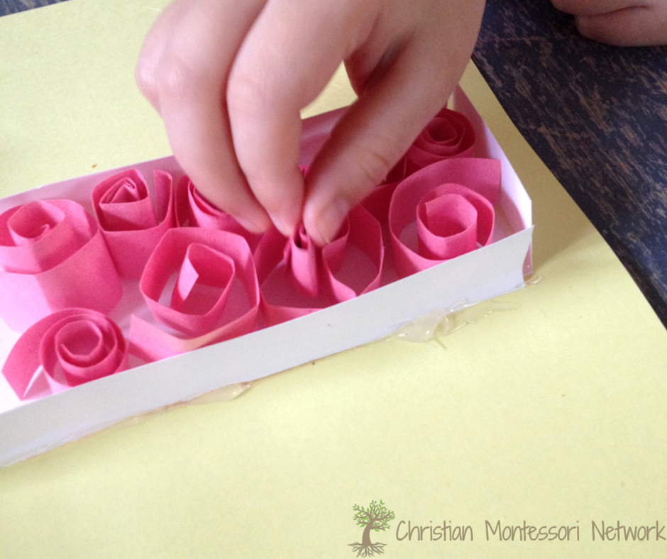 Placing the roses in the cross for this sweet Bible School Craft Idea. Part of a series of  ABCs of the Bible Crafts for kids